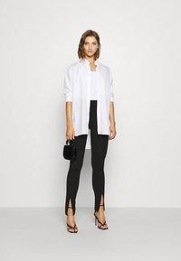 NA-KD - FRONT SLIT PANTS - Trousers - black - 1