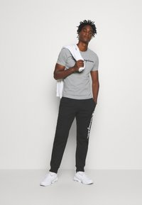 Champion - LEGACY CUFF PANTS - Tracksuit bottoms - black - 1