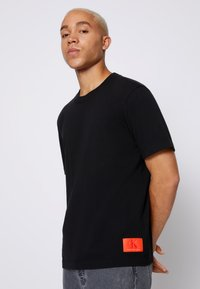Calvin Klein Jeans - RELAXED BADGE TEE UNISEX - Print T-shirt - black - 0