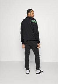 adidas Originals - SWAROVSKI TRACK UNISEX - Chaqueta de entrenamiento - black/shock lime - 2