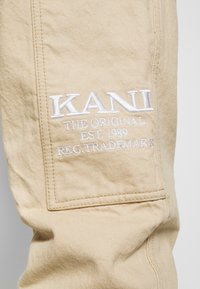 Karl Kani - RINSE BLOCK PANTS - Relaxed fit jeans - beige - 3