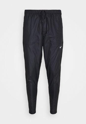 SHIELD - Tracksuit bottoms - black/reflective silver