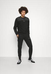 Calvin Klein - REFLECTIVE PRINT - Pantaloni sportivi - black - 1