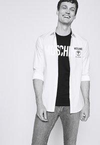 MOSCHINO - Camiseta estampada - black - 3