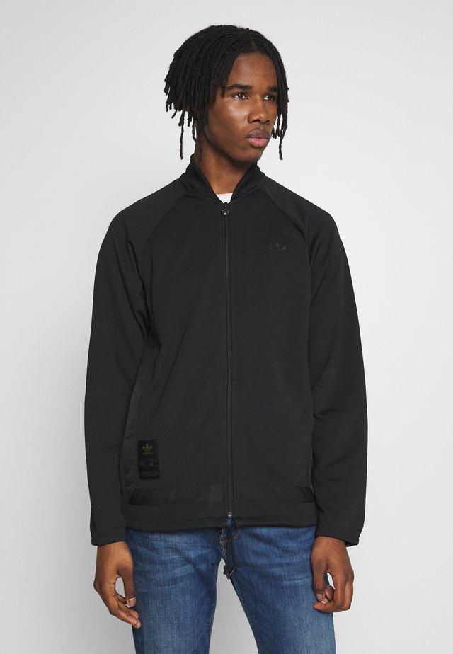 WARMUP - Training jacket - black/goldmt