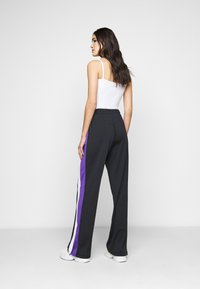 Fila Tall - BECCA TRACK PANTS OVERLENGTH - Verryttelyhousut - black/ultra violet/bright white - 2