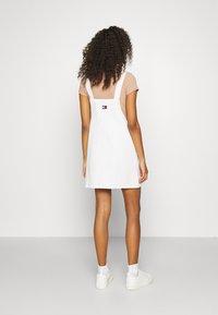 Tommy Jeans - SHORT DUNGAREE SNAP DRESS - Denim dress - work white rigid - 2