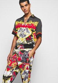 Versace Jeans Couture - TECNO PRINT BELT PAISLE - Tracksuit bottoms - rosso - 3