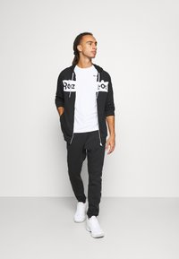 Reebok - TAPE JOGGER - Tracksuit bottoms - black - 1