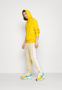 Nike Sportswear - Tracksuit bottoms - grain/white/coconut milk - 1