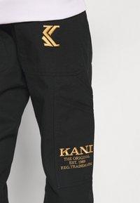 Karl Kani - OG PANTS UNISEX - Cargo trousers - black - 3