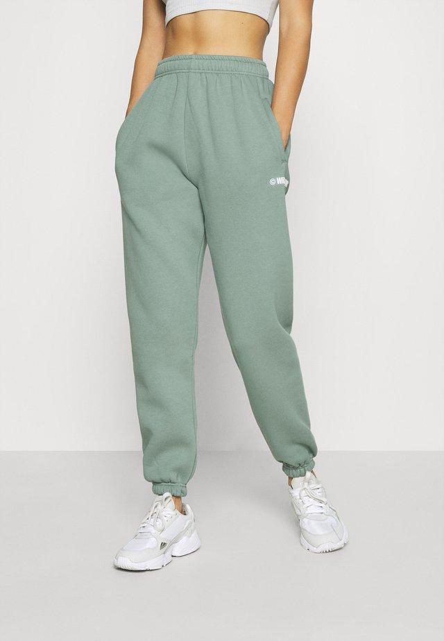 HARVEST PANTS WOMEN - Tracksuit bottoms - green