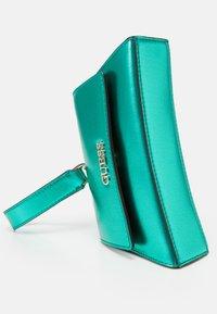 Guess - DEVIN CROSSBODY WRISTLET - Handbag - green - 4