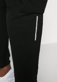 Nike Performance - Tracksuit bottoms - black - 3