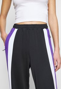 Fila Tall - BECCA TRACK PANTS OVERLENGTH - Verryttelyhousut - black/ultra violet/bright white - 4