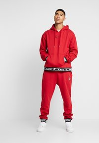 Karl Kani - RETRO TRACKPANTS - Pantalon de survêtement - red - 1