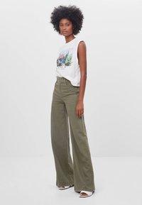 Bershka - MIT WEITEM BEIN - Flared Jeans - green - 1