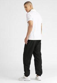 Lacoste Sport - TENNIS PANT - Pantalon de survêtement - black - 2