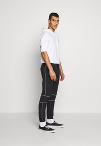 Jack & Jones - JJINEEDO PANTS - Pantalones deportivos - black - 1