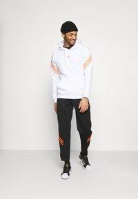 adidas Originals - TRACK PANT UNISEX - Tracksuit bottoms - black/trace orange - 1