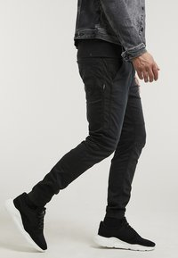 CHASIN' - RESA.L THOR - Trousers - black - 2