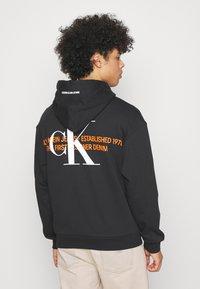 Calvin Klein Jeans - URBAN GRAPHIC LOGO HOODIE UNISEX - Bluza z kapturem - black - 2