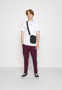 Nominal - CHECK TAPE  - Pantalon de survêtement - burgundy - 1