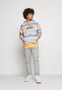 adidas Originals - HOODY UNISEX - Sweatshirt - hazy orange/multicolor - 1
