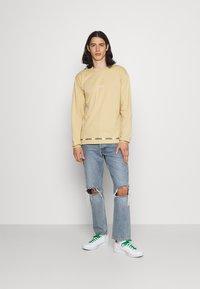 adidas Originals - LINEAR REPEAT ORIGINALS LONG SLEEVE - Long sleeved top - hazy beige - 1