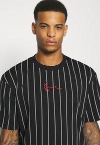 Karl Kani - SMALL SIGNATURE PINSTRIPE TEE UNISEX - T-shirt med print - black/white - 3