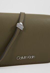 Calvin Klein - MELLOW SADDLE BAG - Sac bandoulière - green - 6