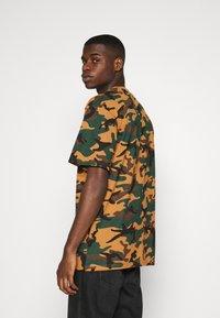 Karl Kani - SMALL SIGNATURE CAMO TEE - Print T-shirt - green/brown - 2