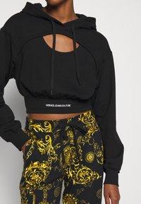 Versace Jeans Couture - PANTS - Tracksuit bottoms - black/gold - 3
