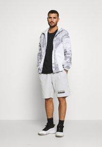 Under Armour - BASELINE SHORT - Sports shorts - halo gray light heather/black - 1