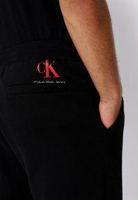 Calvin Klein Jeans - BADGE PANT - Tracksuit bottoms - black - 4