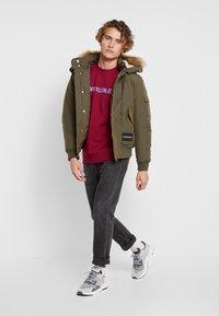 Calvin Klein Jeans - FUR TRIMMED HOODED DOWN BOMBER - Down jacket - dark green - 1