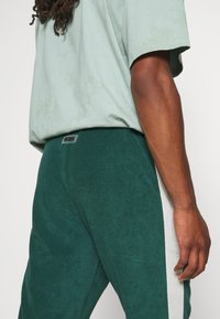 WRSTBHVR - TRACKPANTS LOUNGIN - Tracksuit bottoms - green/off white - 5