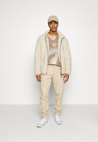 Karl Kani - RINSE BLOCK PANTS - Relaxed fit jeans - beige - 1