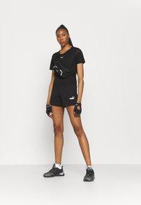 Puma - PAMELA REIF X PUM TEE BACK CUTOUT - Print T-shirt - black - 1