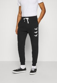 Hollister Co. - ICONIC PRINT JOGGER - Tracksuit bottoms - black stack gull - 0