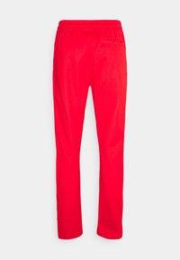 adidas Originals - BECKENBAUER UNISEX - Tracksuit bottoms - red - 6