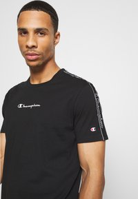 Champion - LEGACY TAPE CREWNECK - Print T-shirt - black - 3