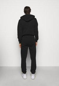 Han Kjøbenhavn - Tracksuit bottoms - faded black/red - 2