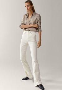 Massimo Dutti - SCHLAG AUS HOHEM  - Flared Jeans - beige - 1