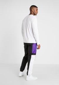 New Era - COLOUR BLOCK TRACK PANT - Teplákové kalhoty - black/true purple/optic white - 2