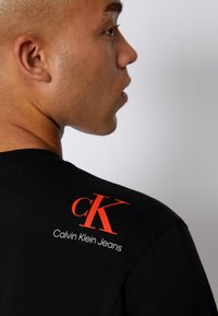Calvin Klein Jeans - RELAXED BADGE TEE UNISEX - Print T-shirt - black - 6