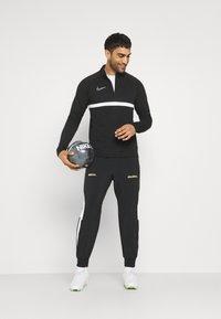 Nike Performance - FC PANT - Tracksuit bottoms - black/white/saturn gold - 1