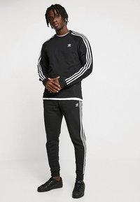 adidas Originals - STRIPES PANT UNISEX - Pantalon de survêtement - black - 1