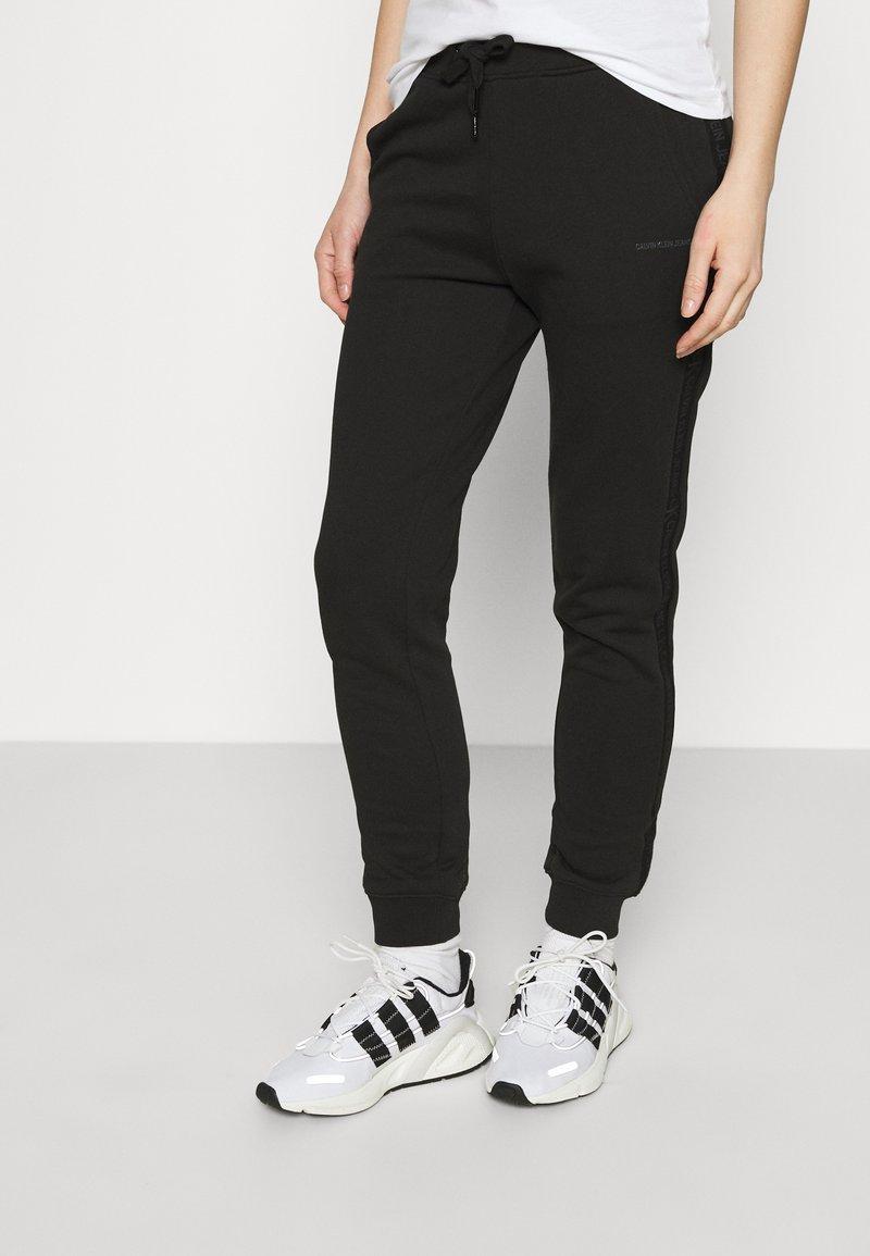 Calvin Klein Jeans - LOGO PANTS - Tracksuit bottoms - black