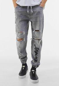 Bershka - MIT PRINT UND ZIERRISSEN  - Jeans Tapered Fit - grey - 0